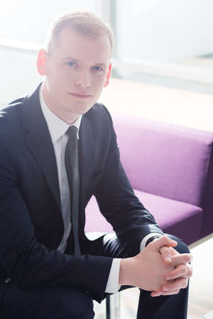 ambitious: Ambitious and confident businessman in suit sitting on sofa Stock Photo
