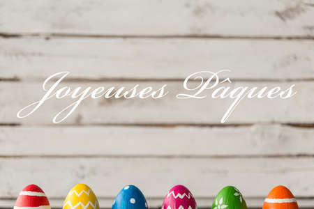 ques: Decorative easter eggs, greetings in french, white planks in the background Stock Photo