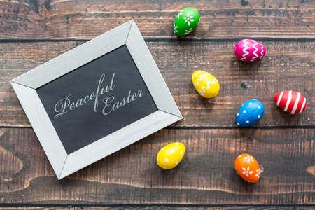 Marco decorativo y huevos de Pascua tumbado en, mesa de madera de color marrón Foto de archivo