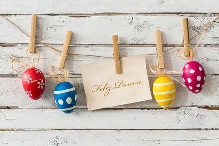 Huevos de Pascua decorativos colgando de una cuerda delgada, tarjeta con deseos en portugués, tablones de luz en el fondo
