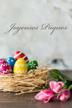 ques: Decoration with easter eggs lying on table next to pink tulips, greetings in french, light background