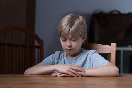 shyness: Shy little boy sitting at the table