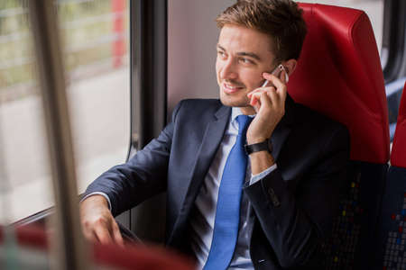 public transport: Young businessman talking the phone in train Stock Photo