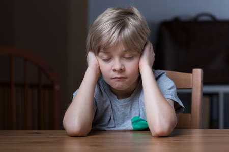 tiresome: Sleepy little boy at the table needs some rest