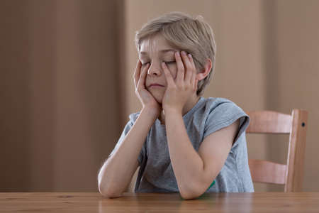 tiresome: Little schoolboy at the table feeling tired