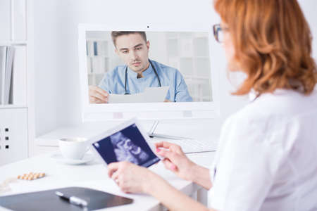 cyber woman: Mature woman doctor holding ultrasound picture during video consultation with another medic, sitting in light office