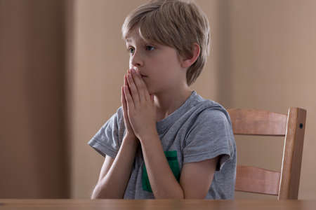 hopeful: Little hopeful boy praying at the table