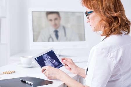 Érett nő orvos, aki ultrahang kép alatt video konzultáció másik orvost, ülve könnyű irodai