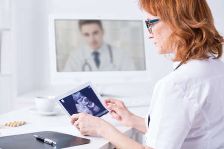 doctor consultation: Mature woman doctor holding ultrasound picture during video consultation with another medic, sitting in light office