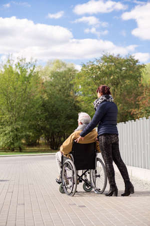 grandad: Image of man on wheelchair with private nurse outdoors Stock Photo