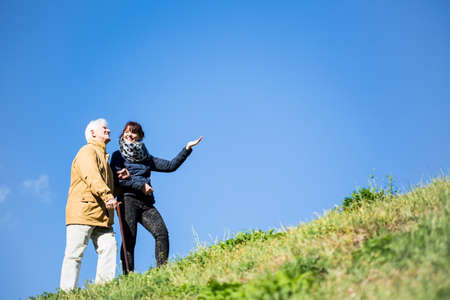 Picture of elderly man relaxing in nature with helpful carer