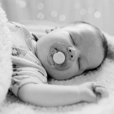 dummy: Calm newborn sleeping with dummy in mouth