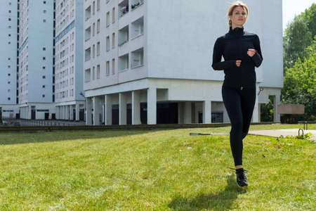 workouts: Woman running on the grass in the city