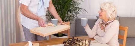 jugando ajedrez: Fotografía recortada de una pareja de ancianos jugando al ajedrez y beber té