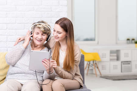 generation gap: Shot of a senior woman listening to music and her granddaughter sitting next to her Stock Photo