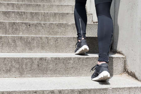 training shoes: Jogging on the stairs - closeup on girls legs