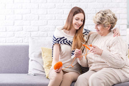 knitting: Shot of a senior woman knitting and her granddaughter observing her Stock Photo