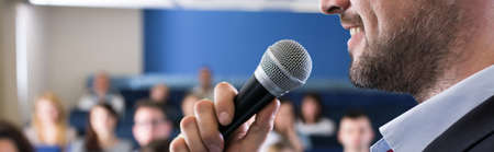business education: Close-up of young elegant man in suit speaking to microphone. Leading classes with students in lecture hall Stock Photo