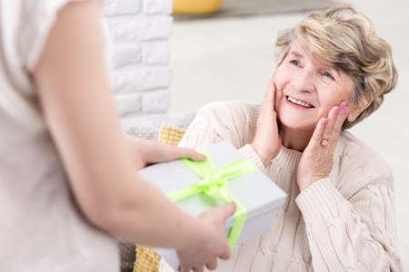 Przycięte zdjęcie młodej kobiety, dając prezent dla swojej babci suprised