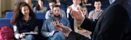 profesor: Los jóvenes estudiantes que escuchan la conferencia con los intereses de la universidad. Primer plano de las manos del joven profesor