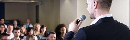 Elegante profesora de mediana edad hablando a los estudiantes durante las clases en la universidad Foto de archivo