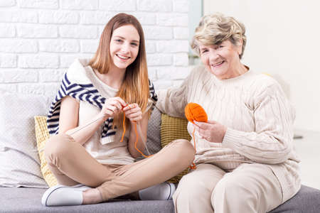 generation gap: Picture of a senior woman showing her granddaughter how to knit