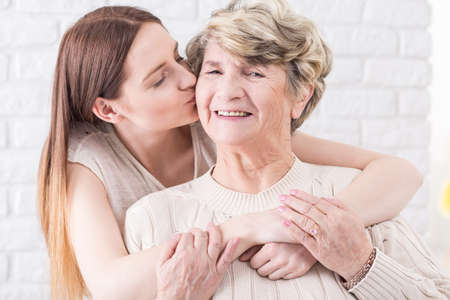 generation gap: Shot of a young woman hugging her grandma