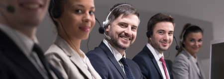 selling service: Group of young busy telemarketers with headset calling the clients and selling products