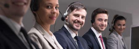 Gruppe von jungen beschäftigt Telemarketing mit Headset, die Kunden fordern und den Verkauf von Produkten Standard-Bild