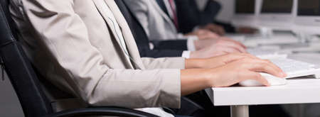 computer operator: Close-up of womans hand and computer on white desk in big corporation. Next to her colleagues sitting by desks Stock Photo