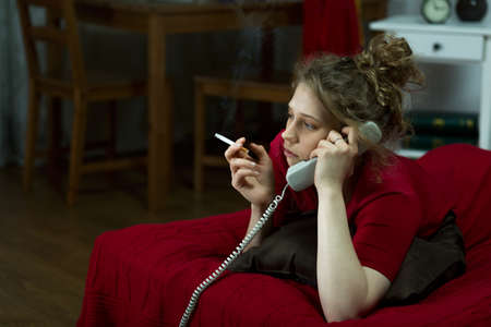 Photo of lonely girl with cigarette and telephone lying Фото со стока