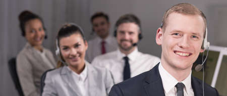happy workers: Team of young elegant counselors wearing headsets working in call center office