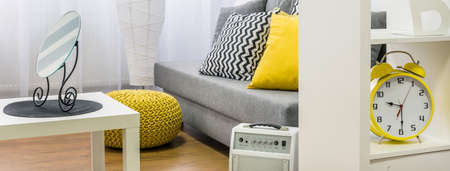 amarillo y negro: Cozy interior in grey, white and yellow, decorative mirror standing on white table, panorama