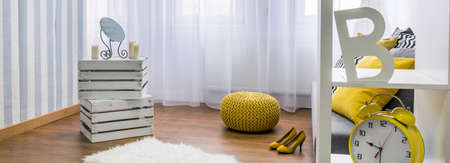 pouffe: Close up of handmade shelf, yellow pouffe and woman yellow high heels, panorama