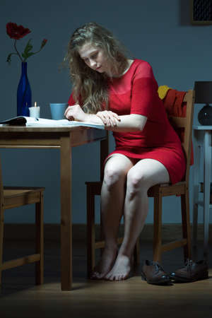 beside table: Photo of lonely girl in red dress sitting beside table