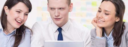 personas trabajando en oficina: Tiro de tres compañeros de trabajo mirando una tableta Foto de archivo