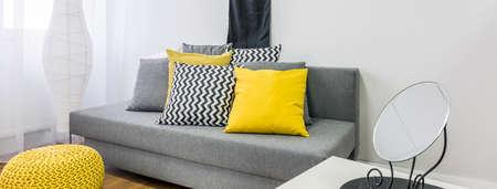 amarillo y negro: Primer plano de un sofá gris con cojines de decoración en negro, amarillo, gris y blanco, panorama