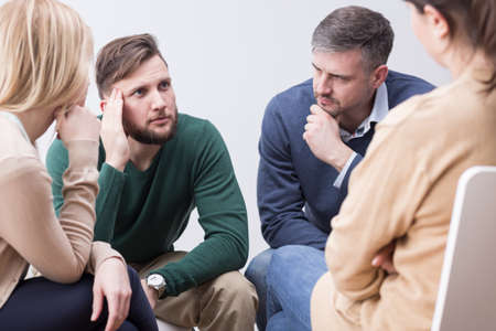 confiding: Troubled young man confiding to his supporting psychotherapy group