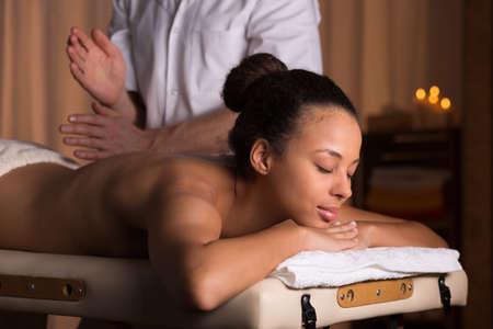 mujeres de espalda: Mujer joven que se relaja después de día duro en el balneario. masajista masculino aplaudiendo la espalda de la mujer