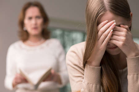Embarrassed broken down teenage girl and her angry mother reading her diary Stock Photo