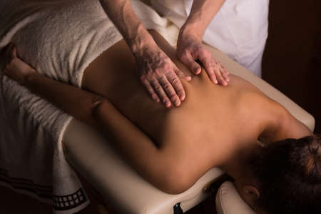therapeutic massage: Masseur kneading the muscles on womans back during therapeutic massage Stock Photo