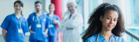 Mooie jonge vrouw in stofdoek beoefenen in het ziekenhuis om een arts te worden. Het werken met collega's en oudere professor