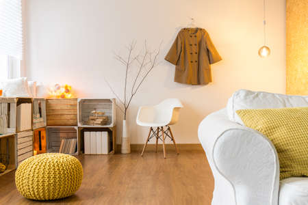 pouffe: Room with flooring and modern furniture Comfortable sofa, chair and yellow pouffe