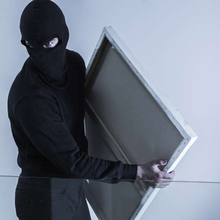 plunder: Photo of masked criminal holding stolen picture