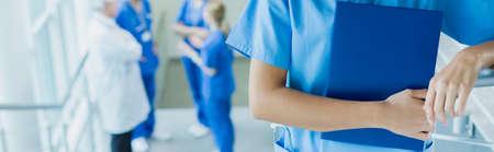 estudiantes medicina: Primer plano de la historia médica del paciente joven médico sosteniendo en caja azul