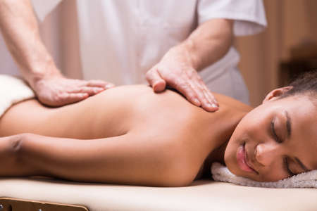 Close-up of masseur stroking womans back during massage Stock Photo