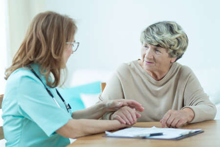 old lady: Trusted doctor is consoling her elder patient