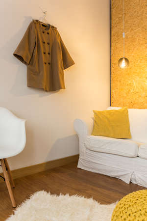 APARTMENT LIVING: Living room with white sofa and chair Clothing hanging on wall Stock Photo