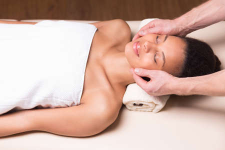 pampering: Pretty young happy woman relaxing and pampering on massage at spa resort Stock Photo