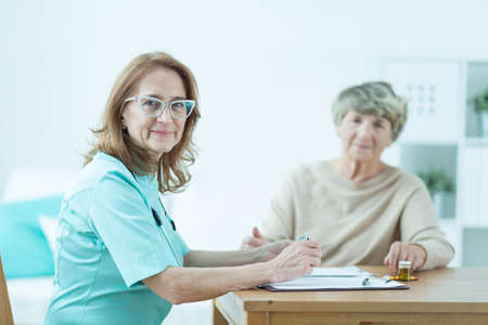 doctor female: Trusted doctor is giving her patient new prescription